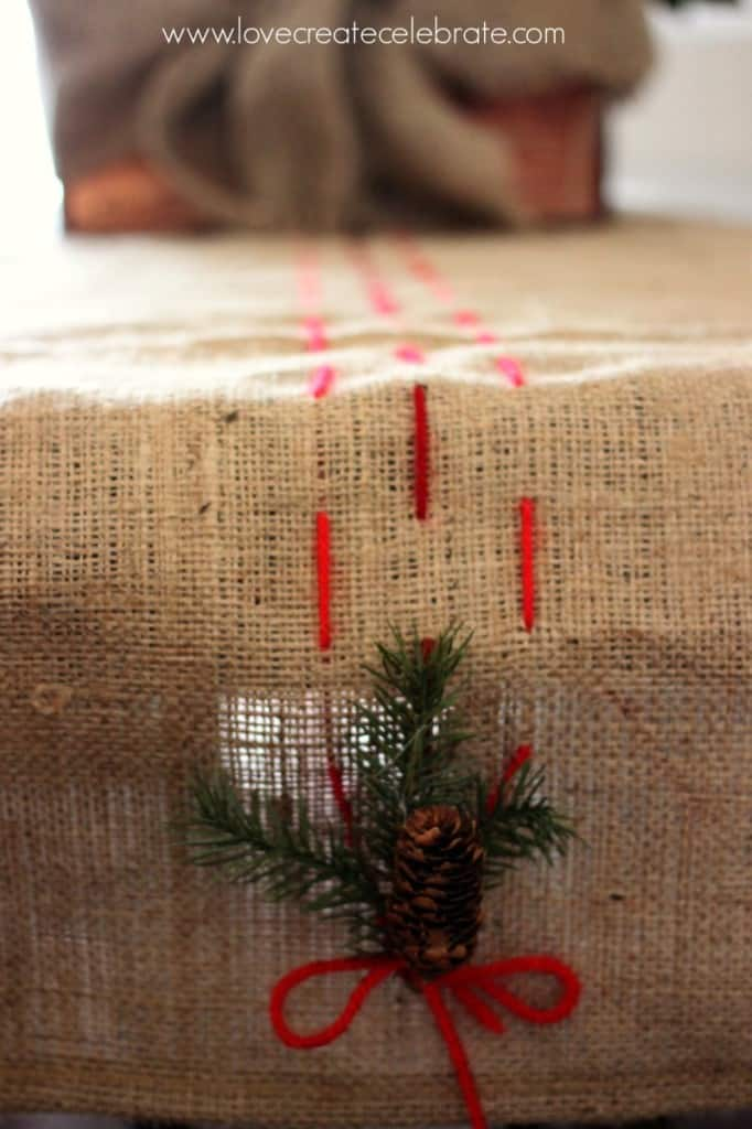Detail of the burlap table runner, with red thread pulling the burlap Christmas decorations together.