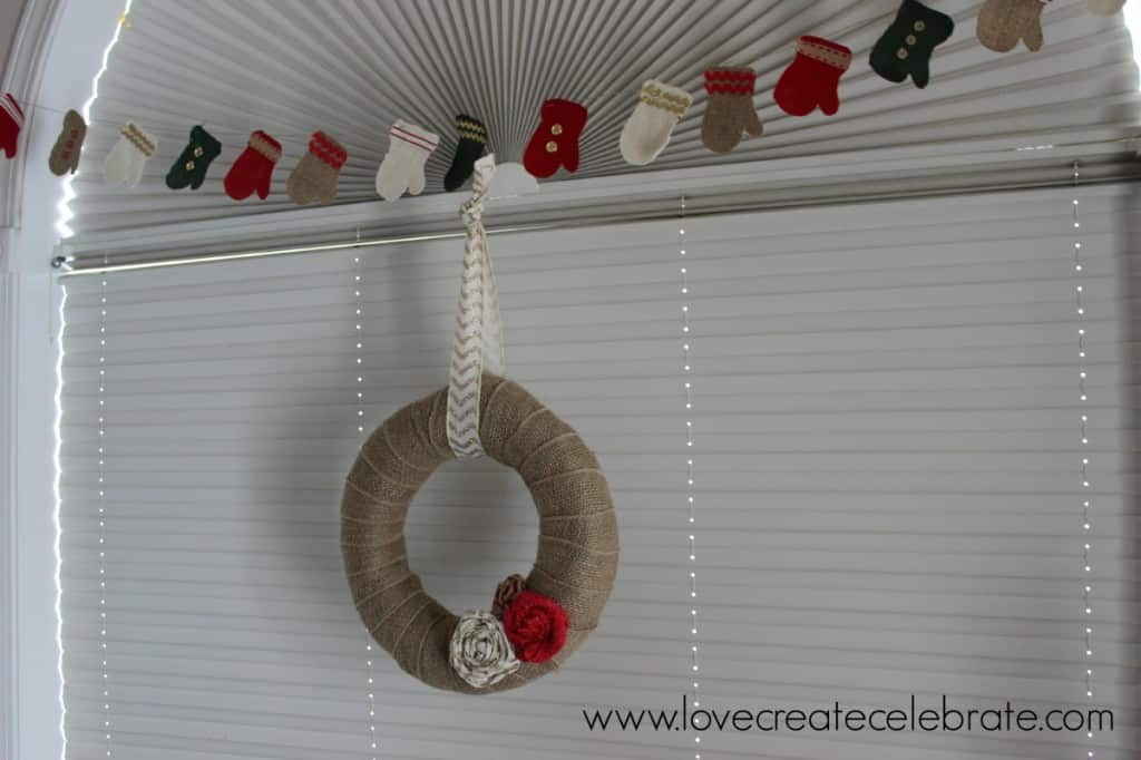 Burlap wreath with a burlap mitten garland above really add to the burlap Christmas decoration theme