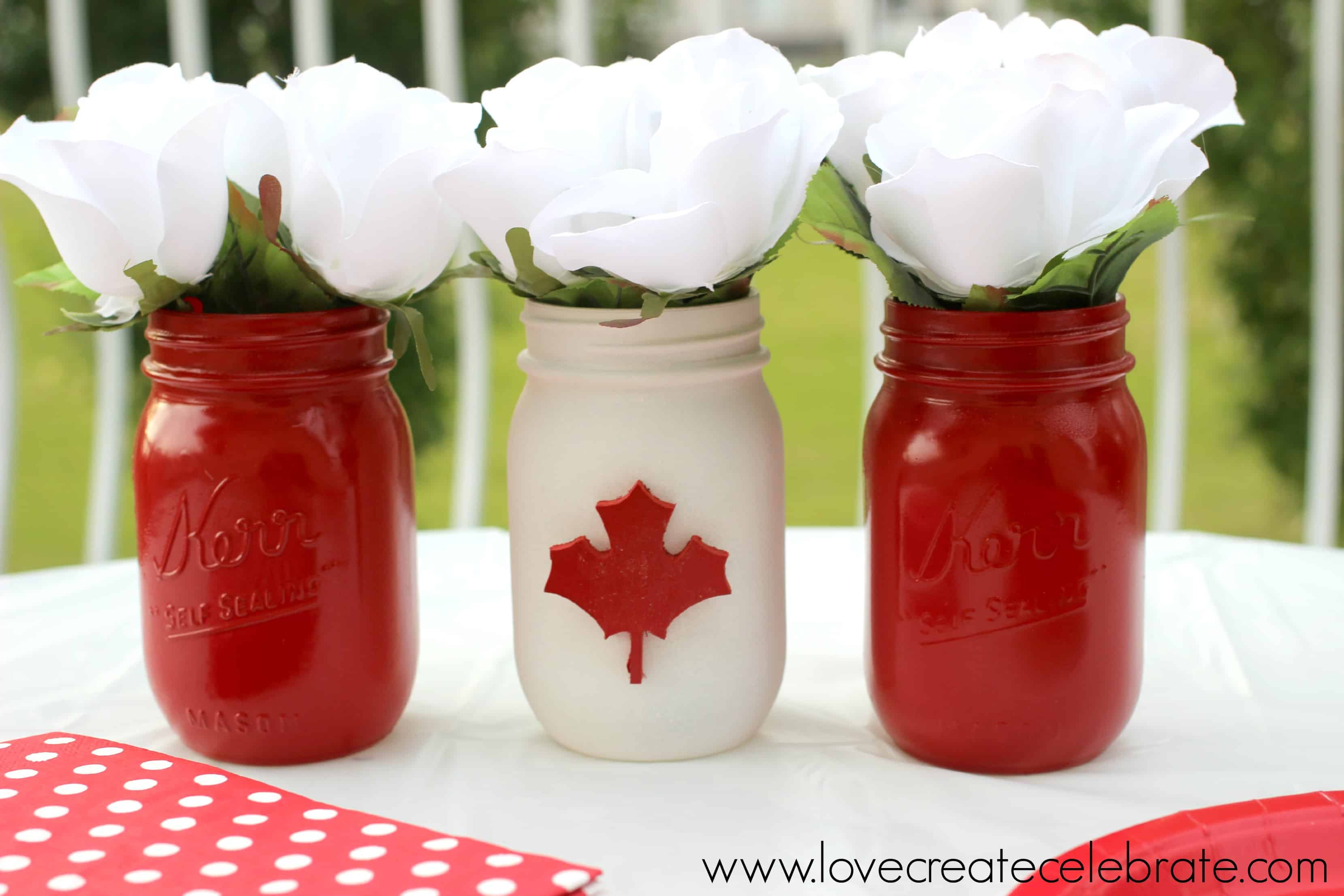 Mason jars painted red, white and red with a red maple leaf on the white painted jar