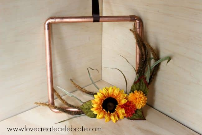 Add some colorful fall foliage to this copper pipe wreath to make it perfect for autumn decor