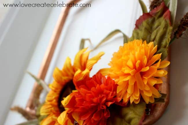 Colorful fall flower give this copper pipe wreath a bright look