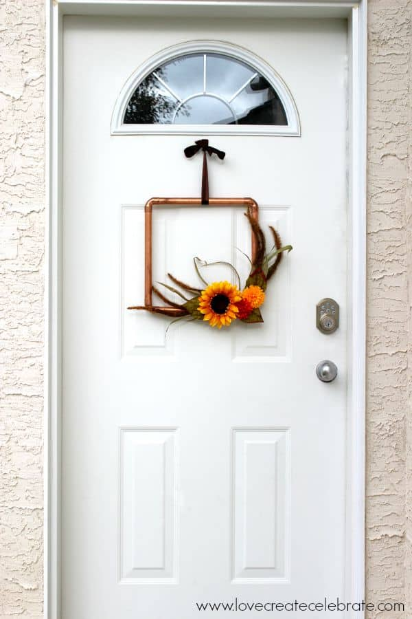 I love the look of this copper pipe wreath on my front door, with just a touch of fall colors