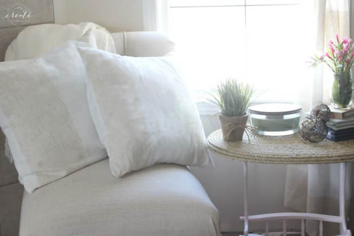 pillows on chair next to table in front of a window
