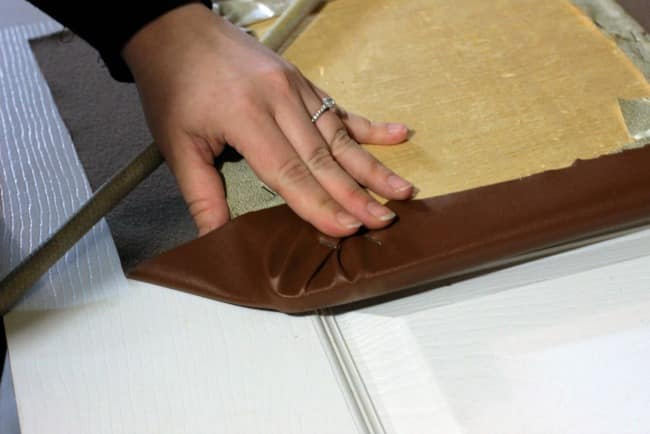 Work one side at a time, folding up and stapling the faux leather in place along the bottom of the cushion