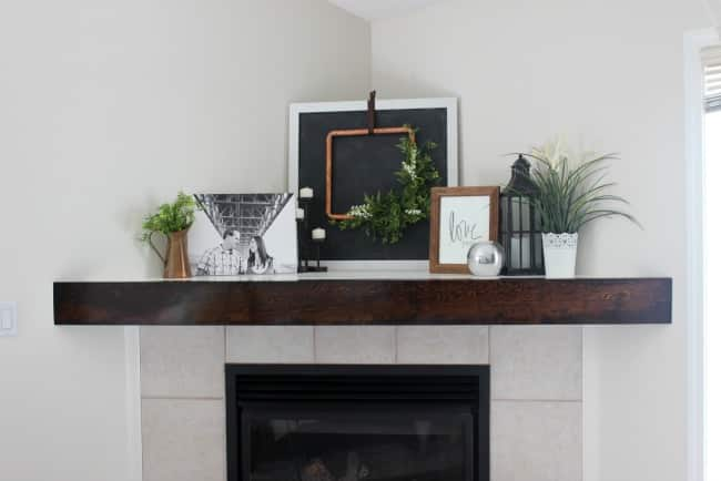 We made this DIY wooden mantel to add a new look to our living room fireplace