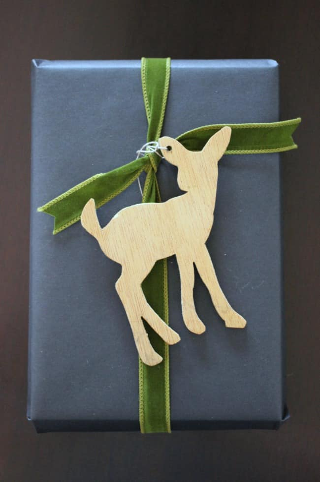 A wooden deer attached to a blue and green wrapped gift