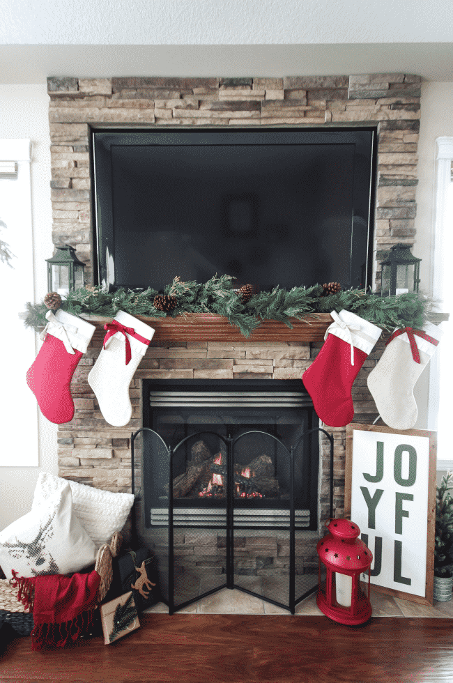 A beautiful rustic fireplace mantel for Christmas! Love the floor to ceiling brick and all of the natural decorations!