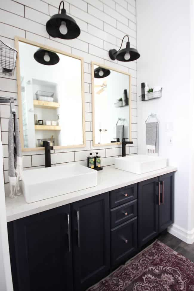 A beautiful modern bathroom renovation with chrome and matte black faucets, sleek modern fixtures and natural wood accents. Beautiful transformation!