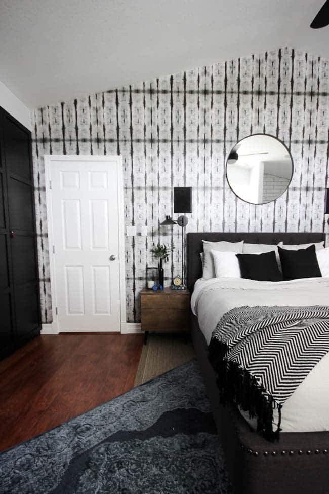 A beautiful Modern Master Bedroom Renovation Reveal! Gorgeous bold wallpaper, black, white and grey tones alongside wooden accent furniture. Ikea cabinets with a sliding barn door. And a white brick fireplace with a dark wooden mantel. Touches of blue and deep red finish the space perfectly. Beautiful transformation!