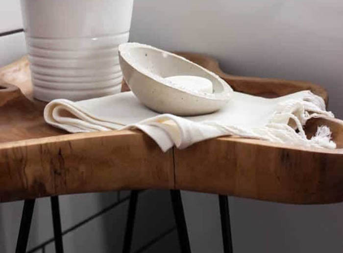 concrete soap dish sitting on small wooden table