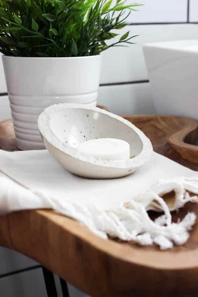 DIY soap dish sitting on small table next to the bathtub