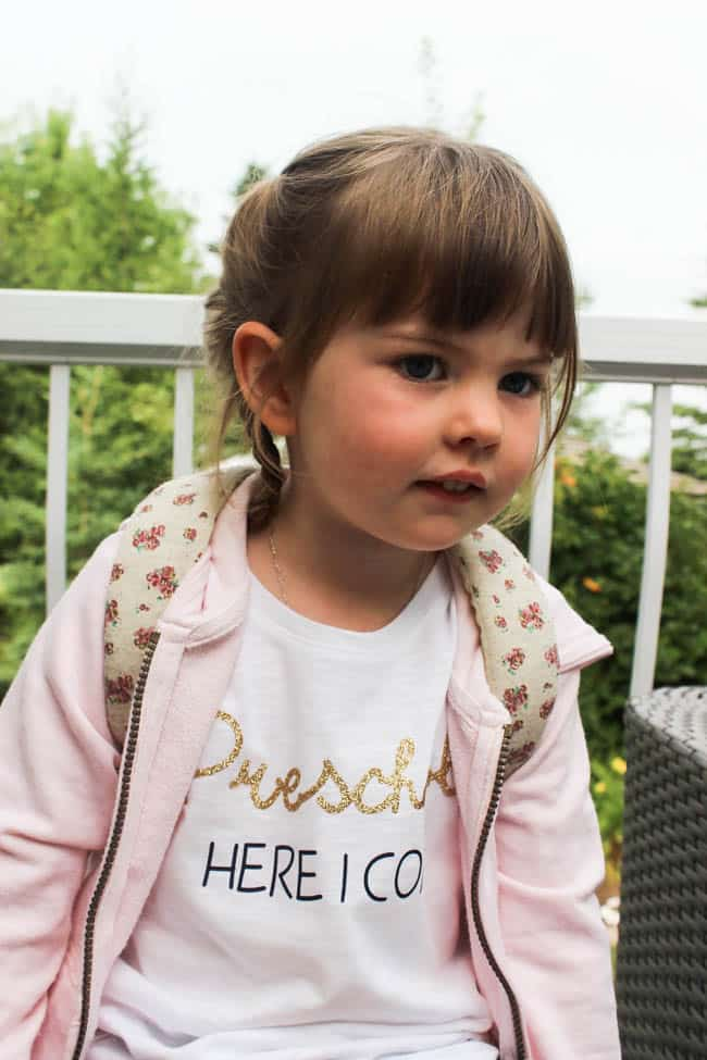 "Little girl wearing first day of school outfit with custom shirt with text ""Preschool here I come"""