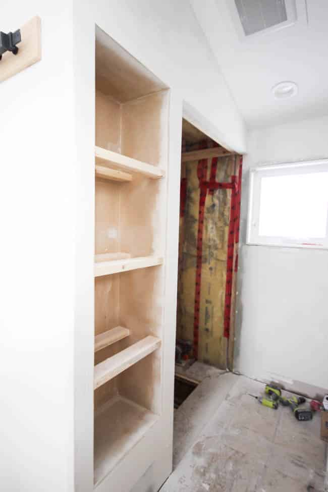 Use drywall putty to blend the shelving into the existing wall space
