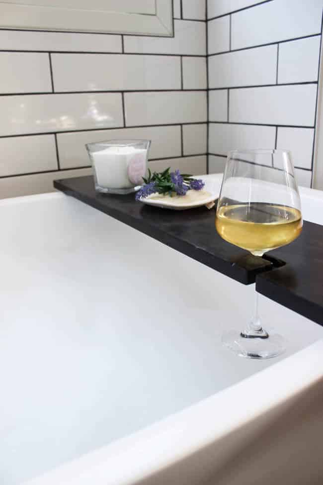 Build your own DIY Bath Table with this simple tutorial! Bath trays are the perfect bathroom accessories to add character and style! Love that this bathtub tray has a wine glass holder too!