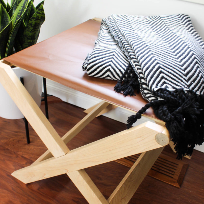Beautiful design on this modern leather bench. Perfect as a bedroom bench or an entryway bench. The natural wood and brown leather make a beautiful combination! Make your own with these FREE build plans!