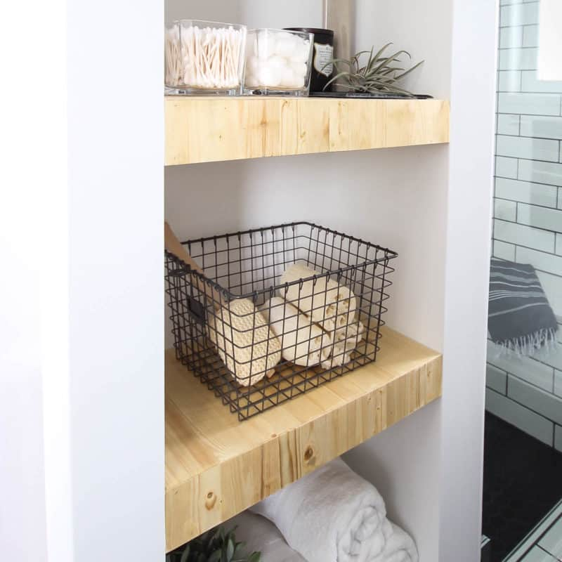 Make your own modern Built-In Shelving with this simple DIY tutorial. Love the natural wood used in this beautiful bathroom renovation! Great tutorial for DIY shelving in the bedroom, living room, or any room!