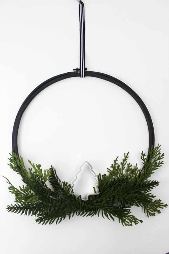 Make this easy embroidery hoop wreath in just five minutes! You just need some spray paint, a bit of greenery, and a cookie cutter!