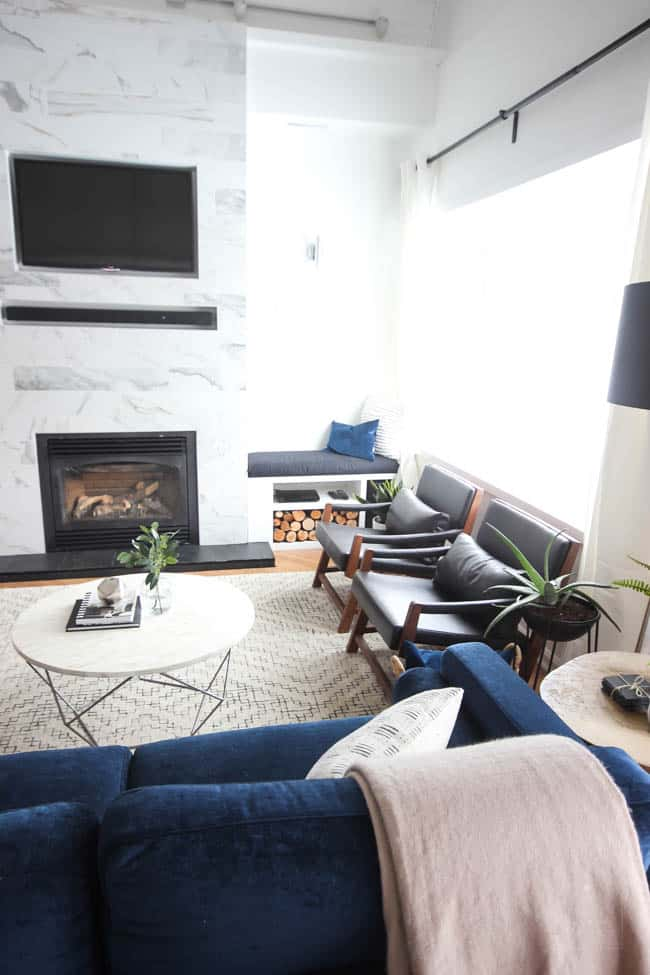 This gorgeous Modern Living Room reveal is finally here! This space came a long way from an outdated, empty space in this beautiful barn home. Love all of the contemporary DIY and decor ideas in this beautiful living space! The tiled fireplace and blue couch are stunning!