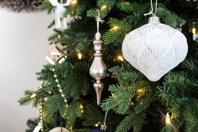 Champagne colored ornaments complement the white and blue theme of this Christmas tree