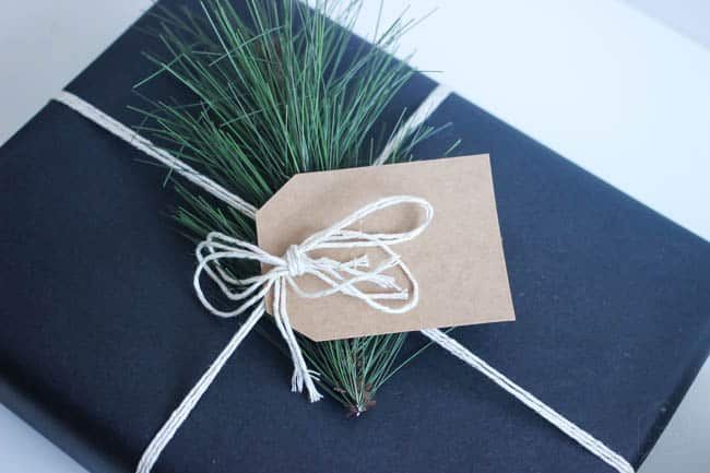 Adding a touch of christmas greenery to this simple DIY gift wrap is a gorgeous extra touch