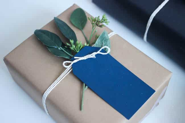 This DIY Christmas gift wrap uses a simple brown wrapping paper, twine, gift tags and holiday greenery