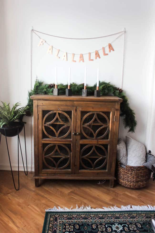 Wooden sideboard decorated with greenery and candles
