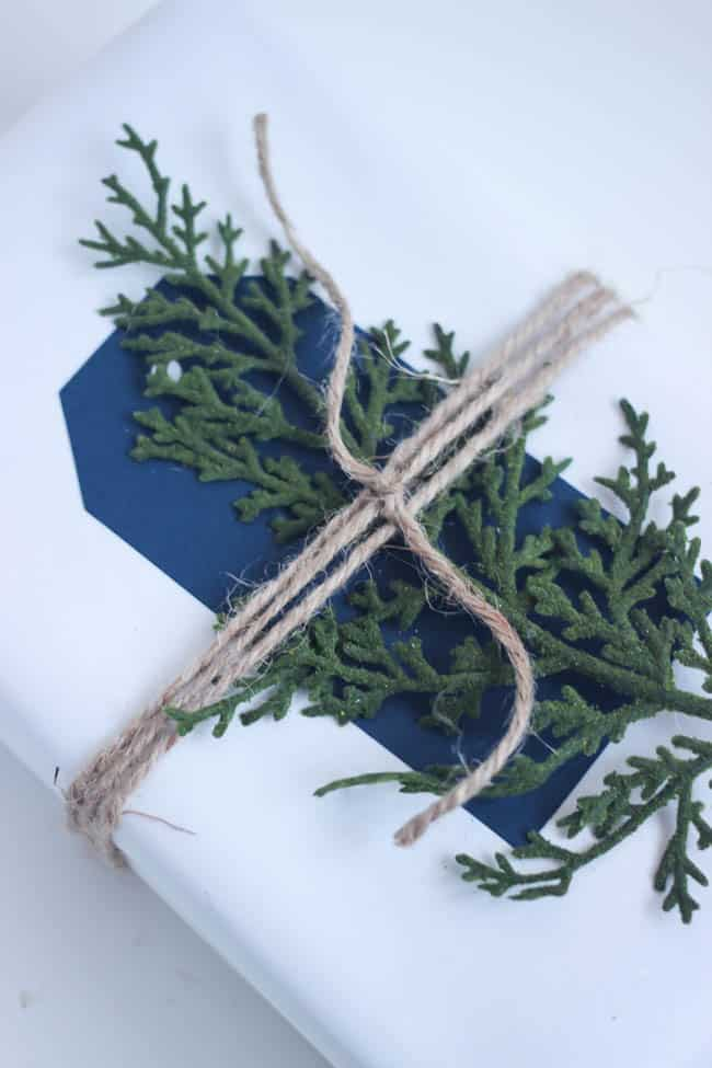 Juniper leaves, twine, and simple gift wrap makes this christmas gift wrap a beautiful minimal decoration