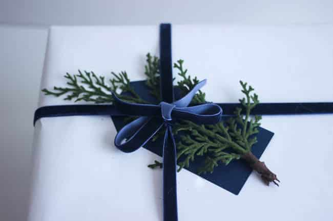 Velvet ribbon with a juniper leaf tucked under is a simple, gorgeous accessory on this Christmas gift wrap