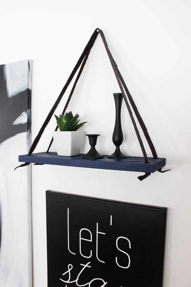 Love this simple modern shelf idea! This simple DIY hanging shelf makes the perfect wall art. If you have some scrap wood and leather you can make this floating shelf in no time!