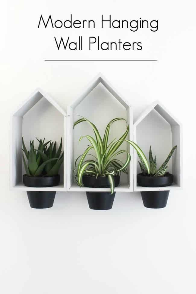 Beautiful Hanging Wall Planters to bring some greenery into your home! Love the modern look of these planters, and the dollar store price tag! Buy the terra cotta pots and wooden houses from the dollar store!