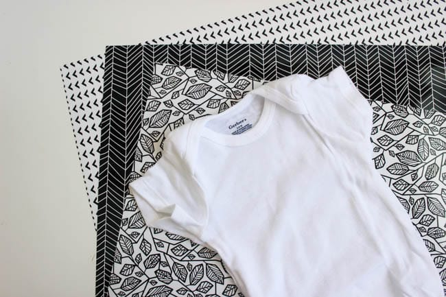 OH! These baby onesies are adorable! LOVE the modern design and the black and white! These DIY onesies were made with Cricut iron on vinyl and the new patterned iron on vinyl. Watch the video tutorial to see how easy it is to make them, and how to use your EasyPress for the heat transfer vinyl.