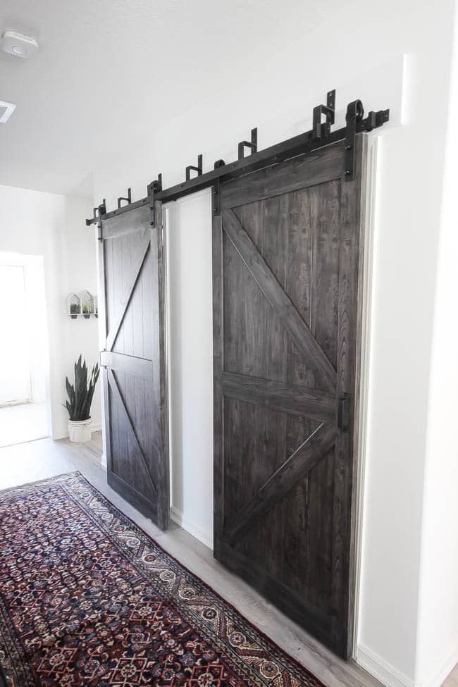 Beautiful hallway decor ideas! Love the eclectic mix of materials and styles in this space. Beautiful light flooring, gorgeous overlapping barn doors, modern artwork, and a vintage hallway runner complete the space. Perfect ideas to fill up a wide hallway!