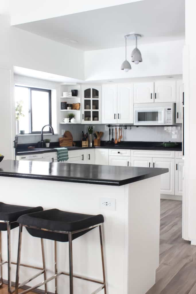 Wow! This stunning modern kitchen was transformed in just one weekend! Love the design ideas in this stunning black and white kitchen! The kitchen features white cabinets, black countertops, black hardware, matte black faucet, black sink, and wood accents. The use of countertop paint and peel and stick tile was brilliant!