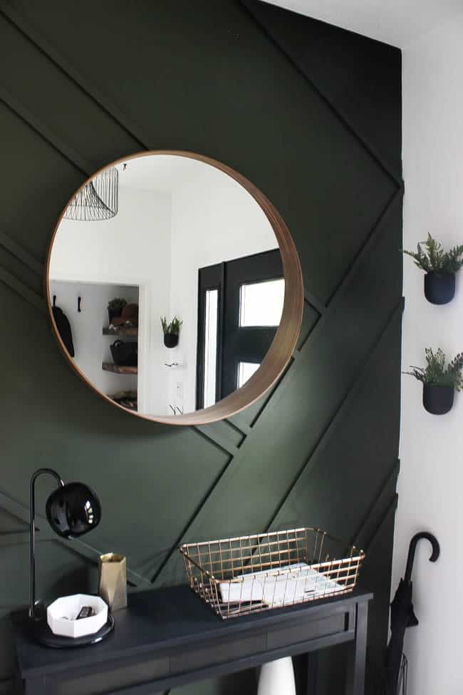 This gorgeous modern entryway reveal is here! What a huge transformation from the outdated space it once was! From the beautiful bench, to the herringbone floors, to the black front door, and the wood accent feature wall. This entry is stunning!