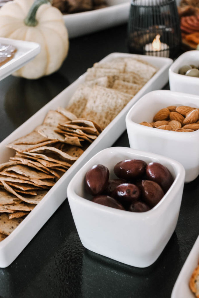 A wide assortment of crackers, nuts, olives, and fruits are essential for a fall themed appetizer spread