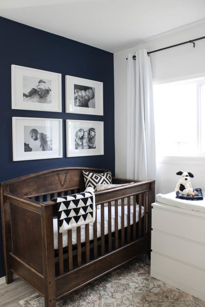 Beautiful ideas for a small nursery! This tiny baby room is off to the side of the master bedroom. Love the simple decor, from the navy wall to the brown crib and the beautiful gallery wall!