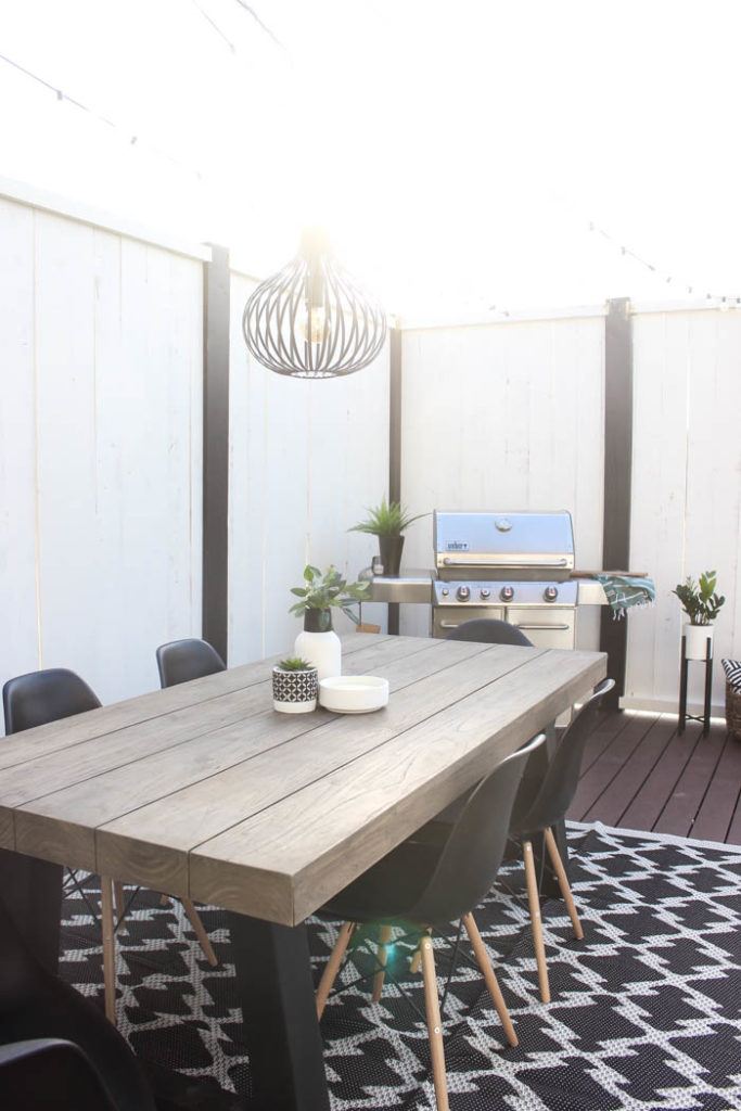 Wow! A beautiful modern outdoor space! The modern table from Article is a stunning addition to this outdoor deck. Finished off with a stunning black and white privacy wall and the gorgeous string lighting!