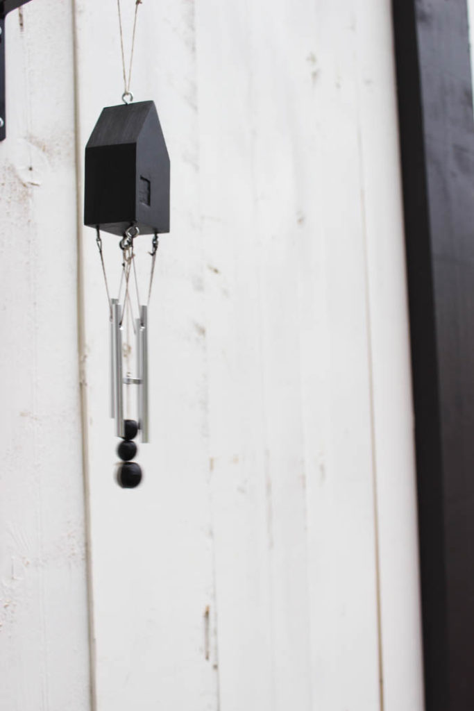 Beautiful modern wind chimes! Add beautiful decor to your outdoor space or deck with this simple thrift store update! Love the miniature houses and the stylish new take on wind chimes!