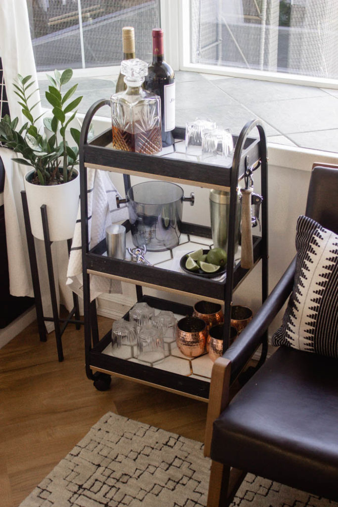 This modern bar cart is stunning! It's hard to believe that this is a DIY! Love the tile inlays and the mix of black, white, and gold in the design. Beautiful bar cart styling and ideas for your home entertaining! #DIY #barcart #tile #luxe #modern