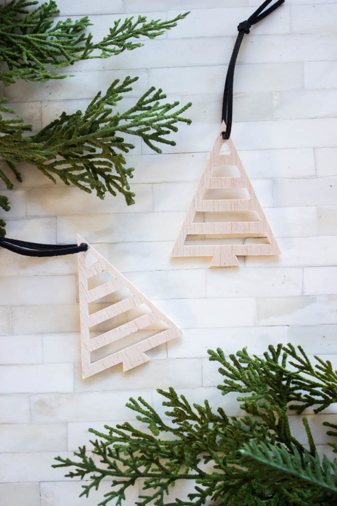 Use the cricut maker to cut these simple christmas tree ornaments from wood