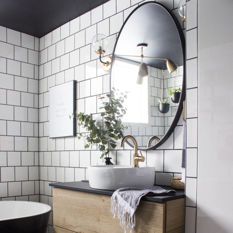 Wow! This modern Bathroom Reveal is absolutely stunning! What a gorgeous space! Everything from the black tub and shower frame, the champagne bronze faucets, and the wood vanity to the black ceiling and built-in storage units! What an incredible transformation! #modernbathroom #paintedceiling #blackceiling #blackandwhite #bathroom #remodel #renovations