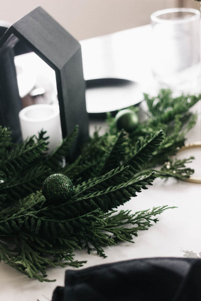 A stunning holiday tablescape and DIY table runner! This beautiful modern table setting was put together with a few affordable painted pieces creating a beautiful dark a moody Christmas table with greens, blacks, and whites. The eucalyptus stamped table runner is gorgeous! #tablescape #Christmas #darkandmoody #Holiday #blackandwhite #tablesetting