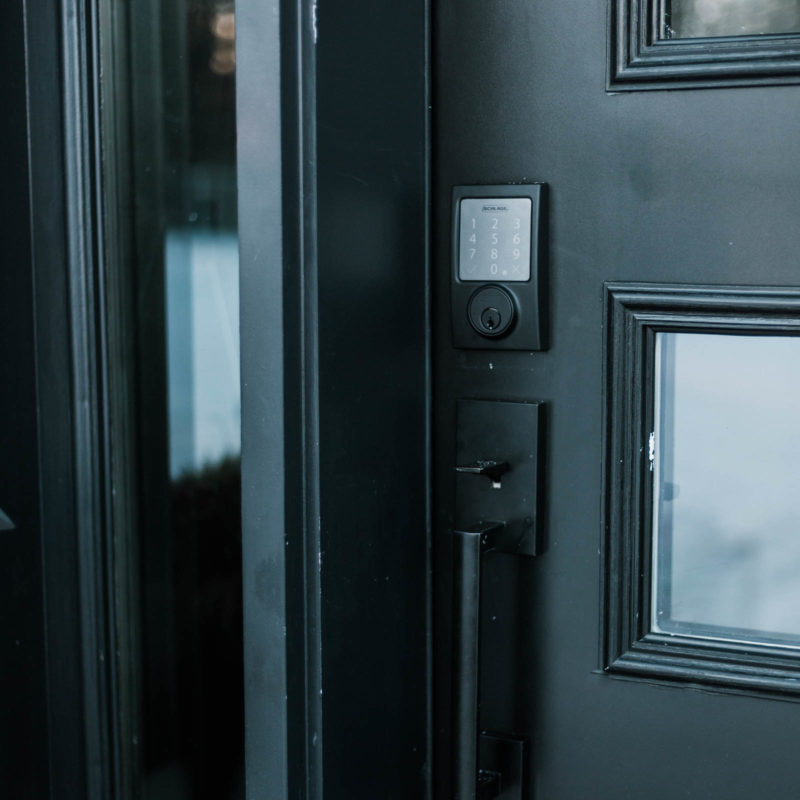 Update your front door with a keyless door lock. These amazing smart locks can be controlled with an app and linked to your Google Home device. Love the matte black lock and hardware on this black door! #smarttechnology #entry #modernentry #keylessentry #hardware