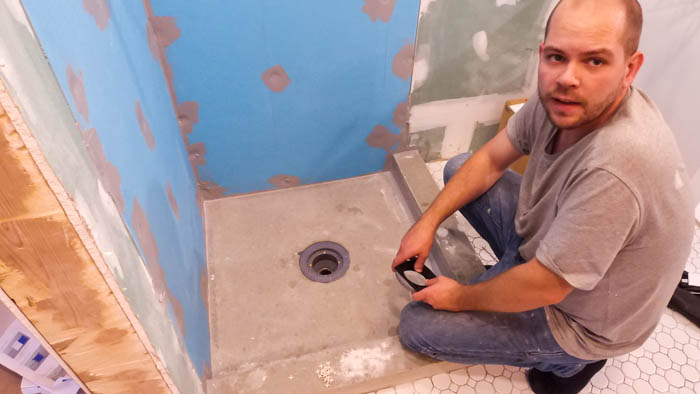 How to install a shower pan and drain. A great video tutorial and step-by-step guide to installing a shower pan or base and drain. Also shares how to install the waterproofing system using the Ubau Flo kit. #renovations #renobloggers