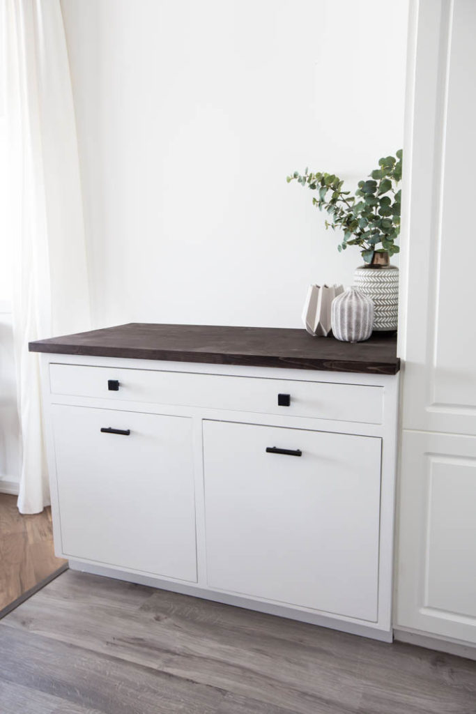 White cabinet with wood top in kitchen