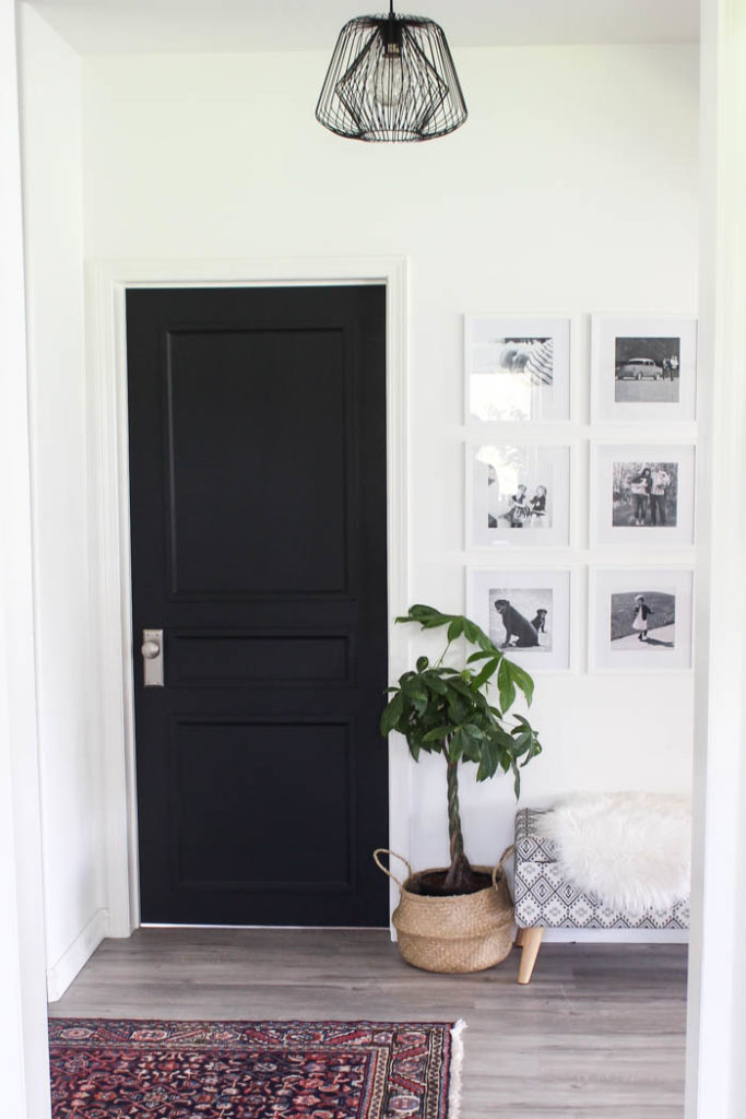 modern hallway with photo gallery, plant, bench, and updated doors