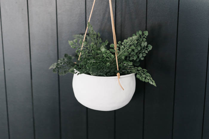 hanging indoor flower pot with black shiplap wall