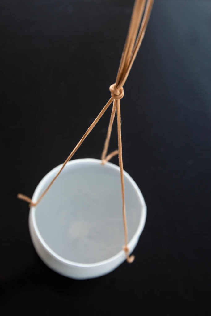tying leather strings for a white flower pot