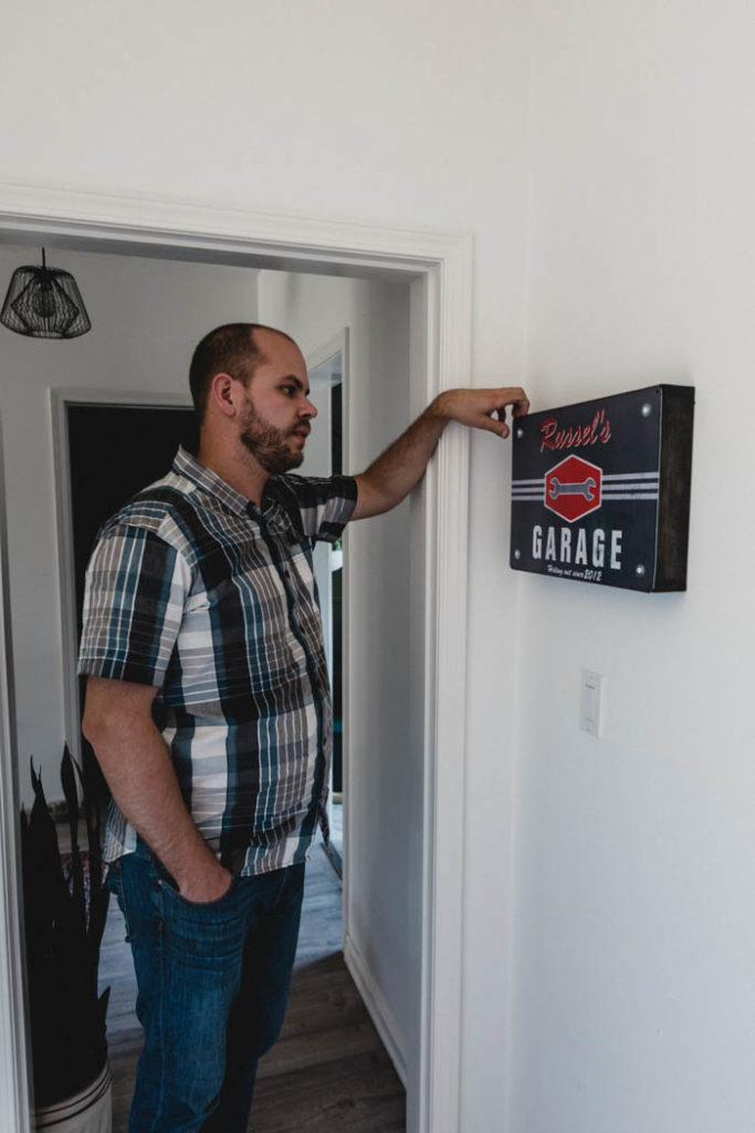 man opening garage sign with hidden storage