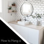 tiled bathroom with text overlay reading, how to hand a mirror on tile